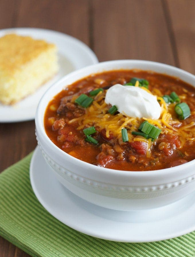 Slow Cooker Chili in a white bowl with cornbread in the background