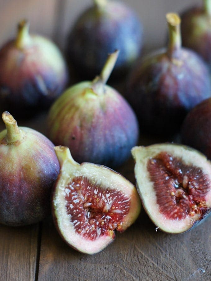 Five fresh figs with one cut in half.