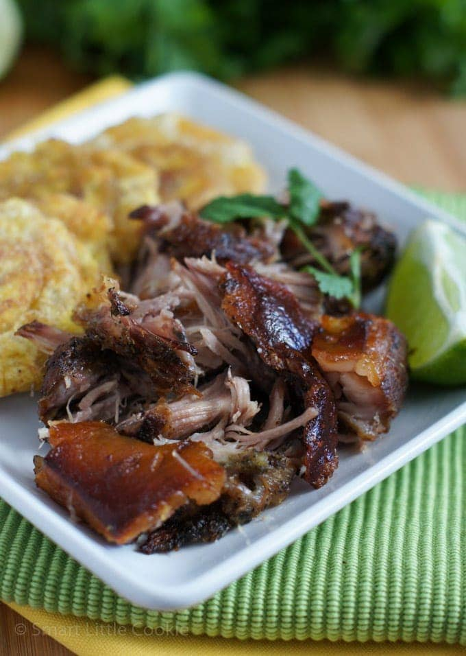 Crispy Roasted Pork Shoulder served on a white plate with a side of tostones