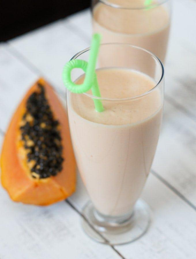 Papaya milkshake in a tall glass with a green straw.