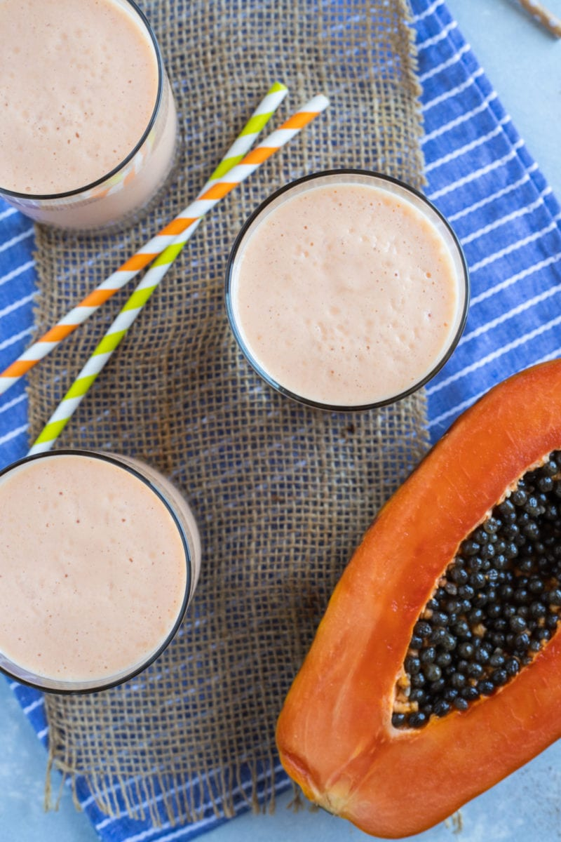 Papaya milkshake (batido de lechosa) served in three glasses and straws on the side.