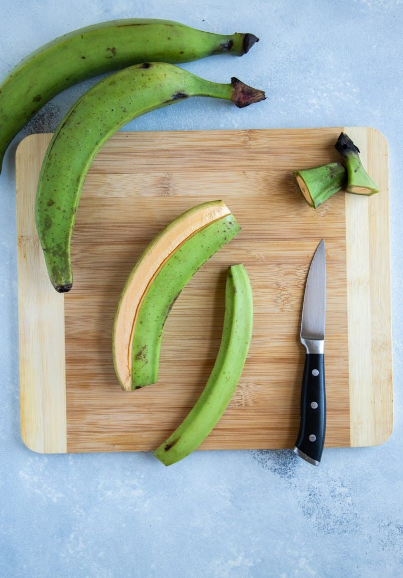 Green plantains being peeled on a kitchen wooden board.