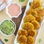 Tostones (Fried Green Plantains) served on a white plate with mayo ketchup sauce and guacamole on the side.