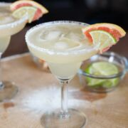 A grapefruit lime margarita in a glass with a salted rim.