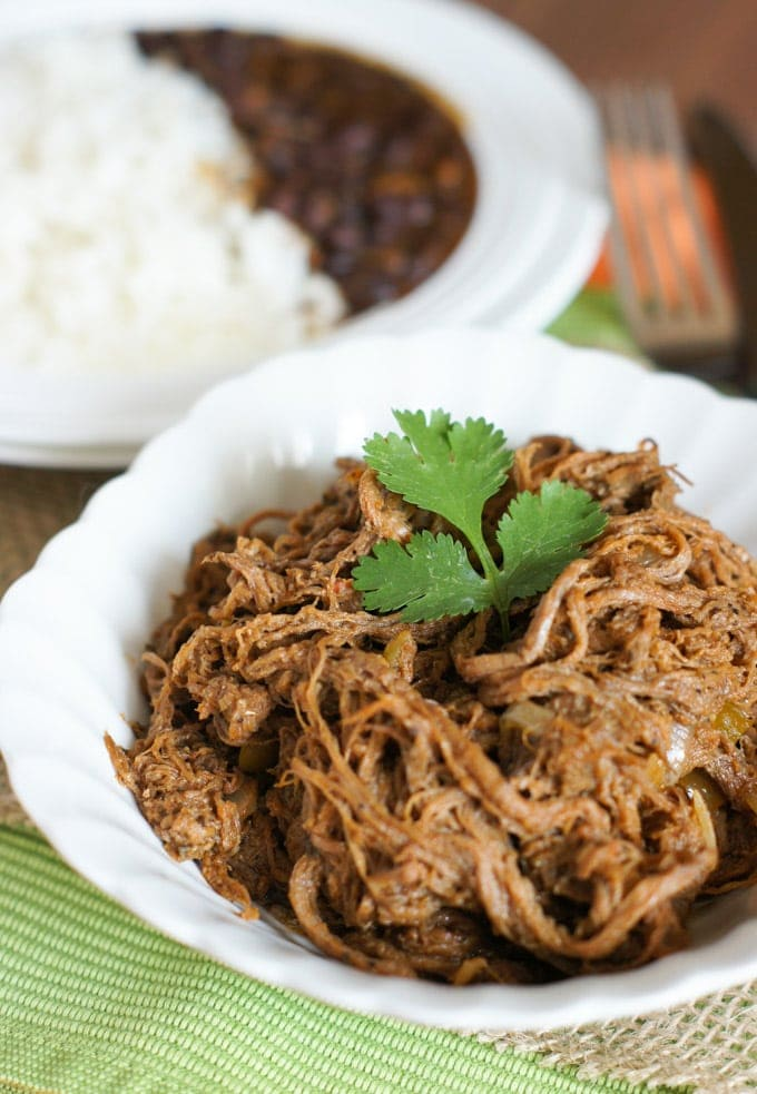 Slow Cooker Shredded Beef (Ropa Vieja) served on a white bowl with white rice and  beans on the side