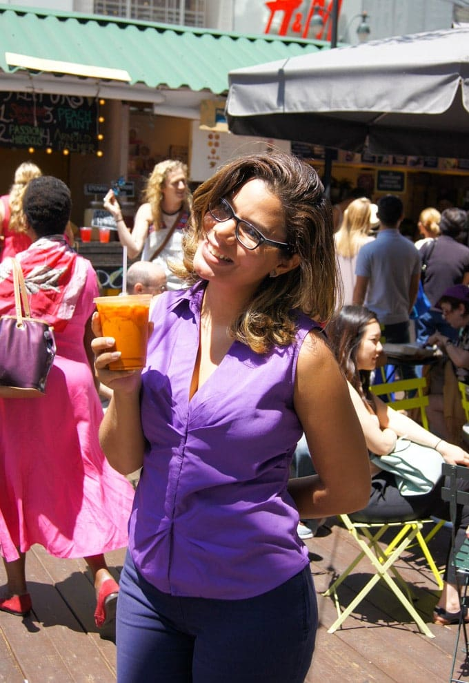 A woman holding an orange drink.