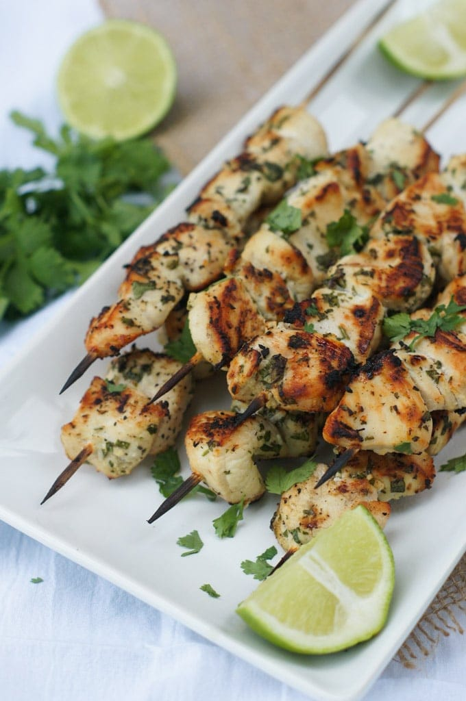 Seven grilled chicken skewers stacked on top of each other on a white plate.