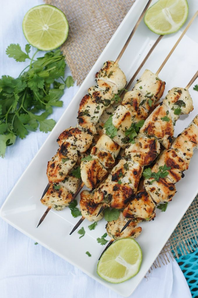 Six garlic chicken skewers on a white plate, garnished with fresh cilantro.