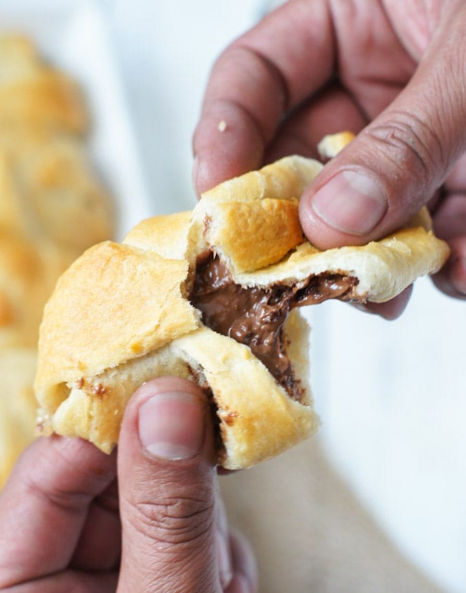 A crescent roll being broken in half to reveal the smores filling.