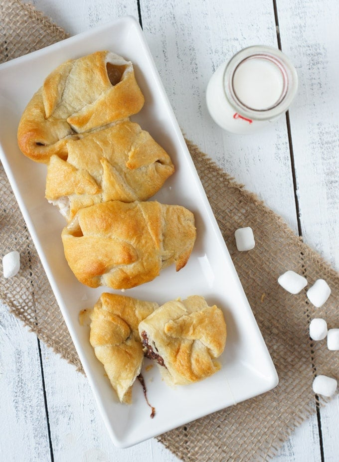 Overhead shot of four smores crescent rolls on a white plate.