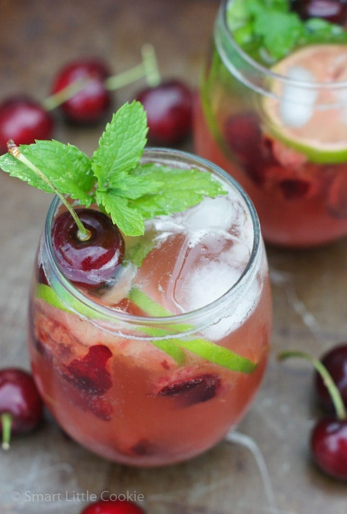 A cherry mojito in a glass garnished with mint and a fresh cherry.