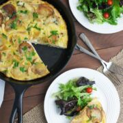 A Spanish tortilla in a skillet with a piece served on a plate with a side salad.