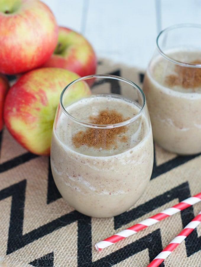 Batido servido en vasos de cristal al lado de manzanas