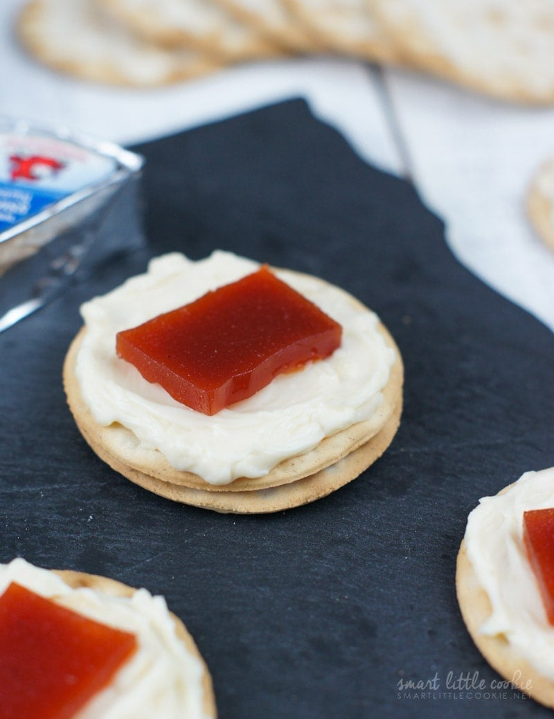 Close up of two crackers topped with cheese and a square of guava.