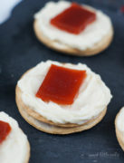 A cracker topped with cream cheese and a piece of guava.