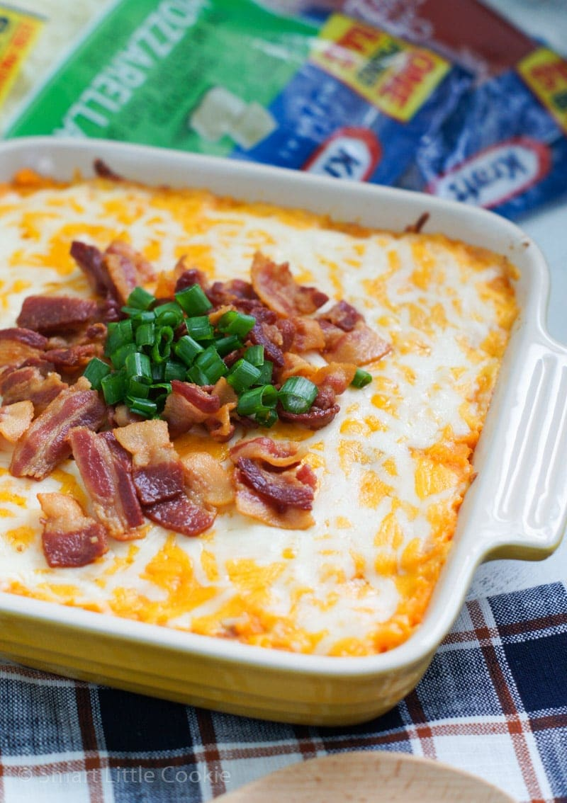 A sweet potato casserole topped with bacon bits and sliced green onion.