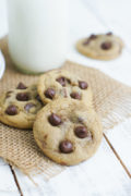 Three chocolate chip cookies on a table mat.