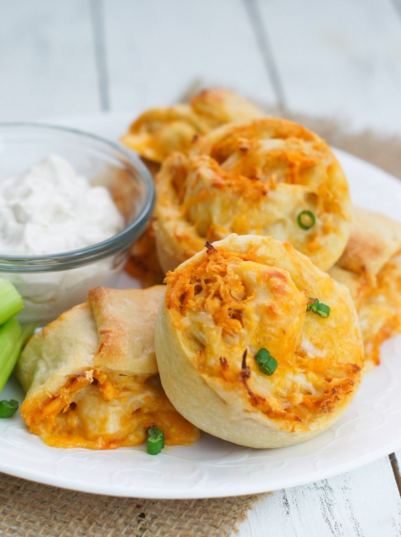 Buffalo chicken rolls garnished with chives and served with a dip.