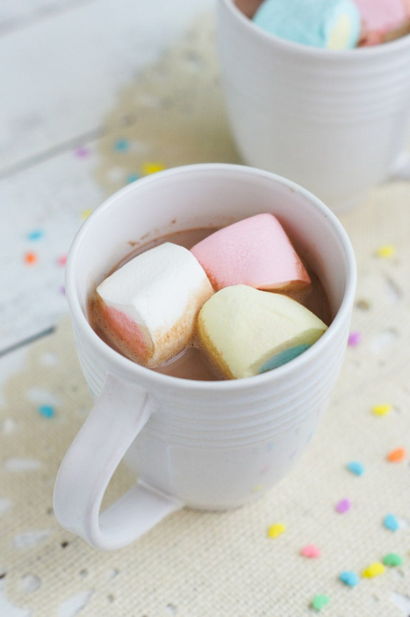Three marshmallows floating in a mug of hot chocolate.