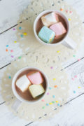 Overhead shot of two mugs of hot chocolate topped with marshmallows.