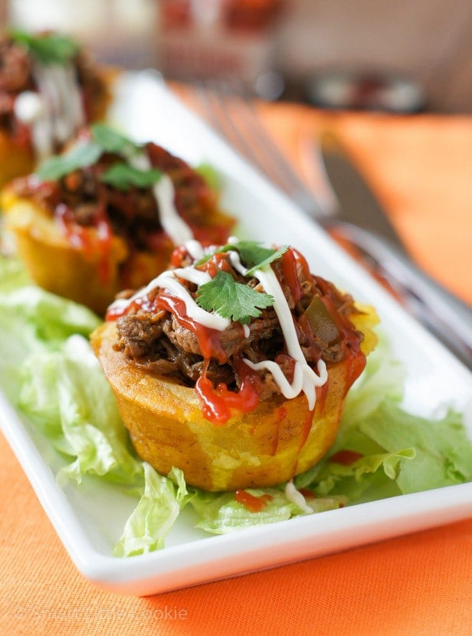 Ropa vieja stuffed plantain cups with mayo and ketchup drizzled on top