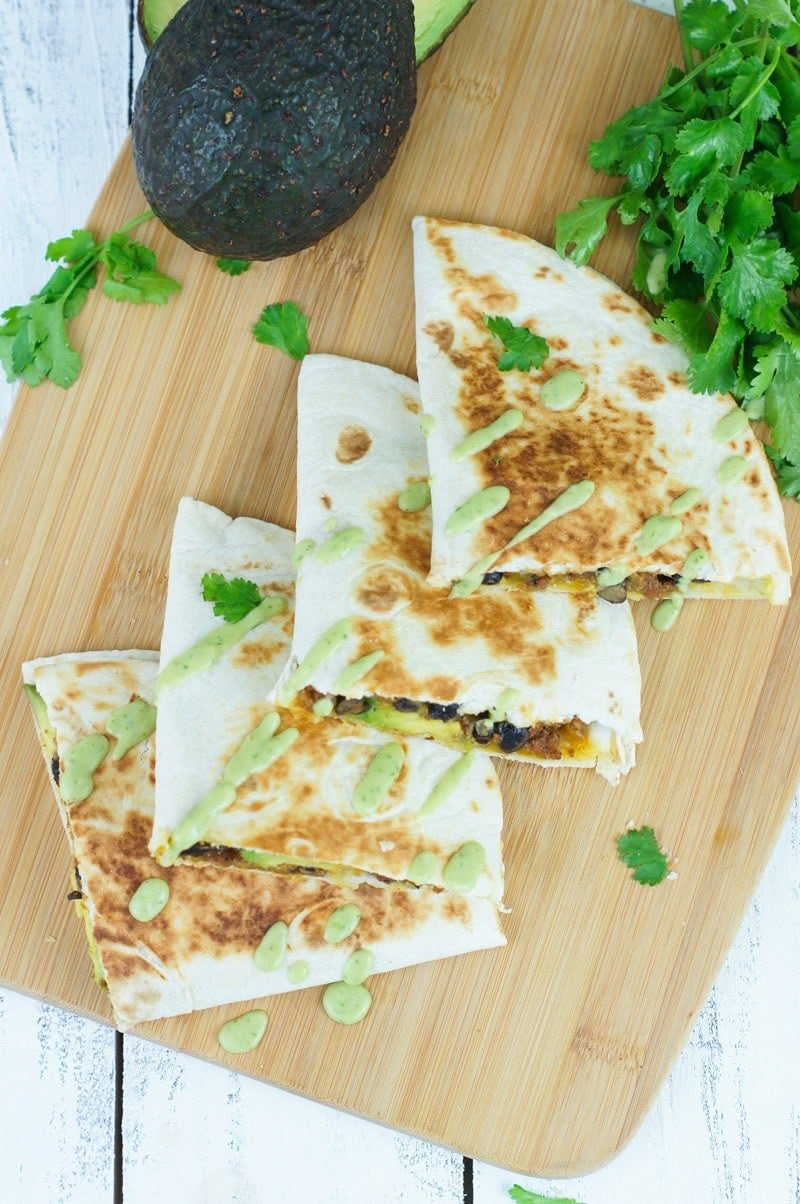 Quesadillas drizzled with a green sauce and garnished with fresh herbs.