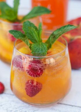 A peach raspberry spritzer garnished with fresh mint.