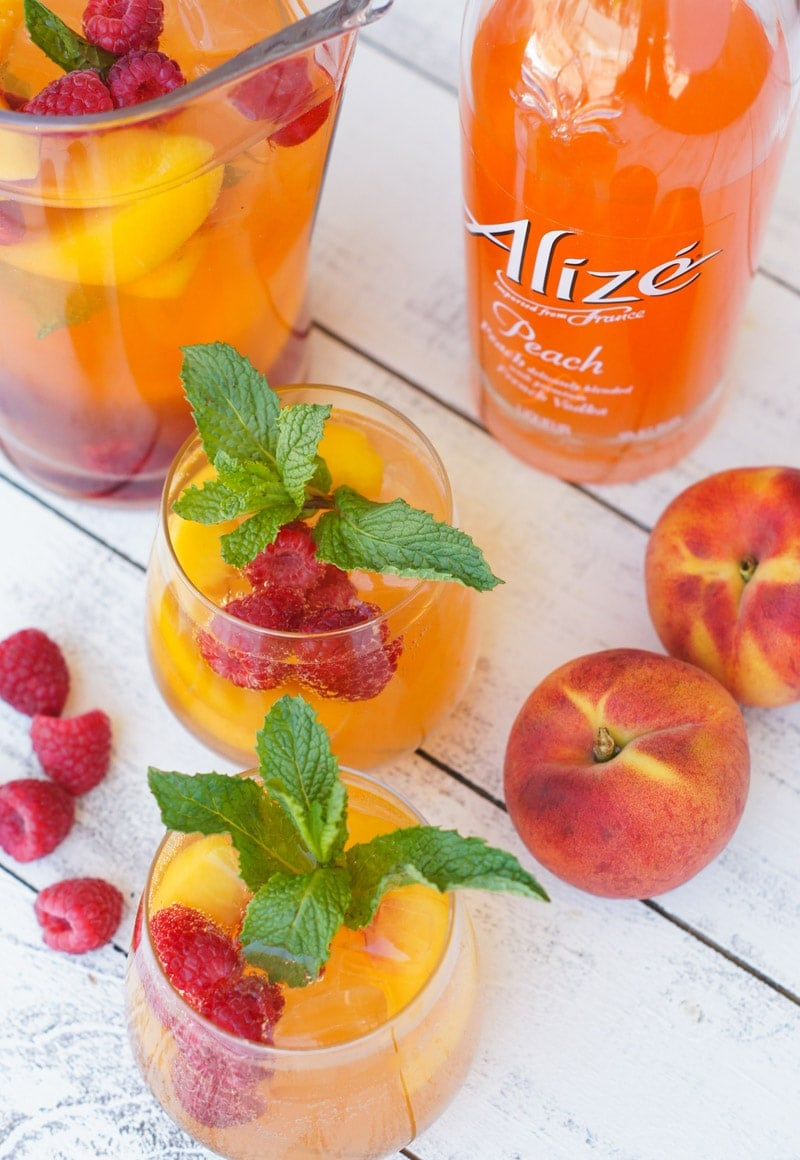 Overhead shot of the spritzers next to fresh fruits and garnished with mint.