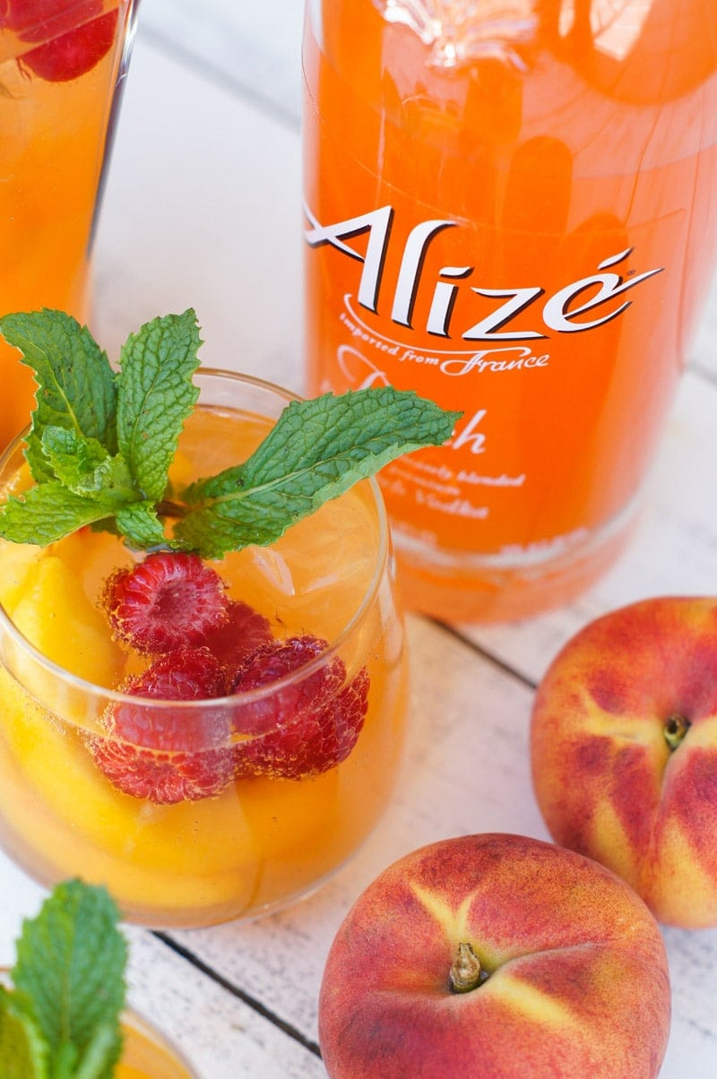 A glass of the spritzer next to a bottle of peach drink.