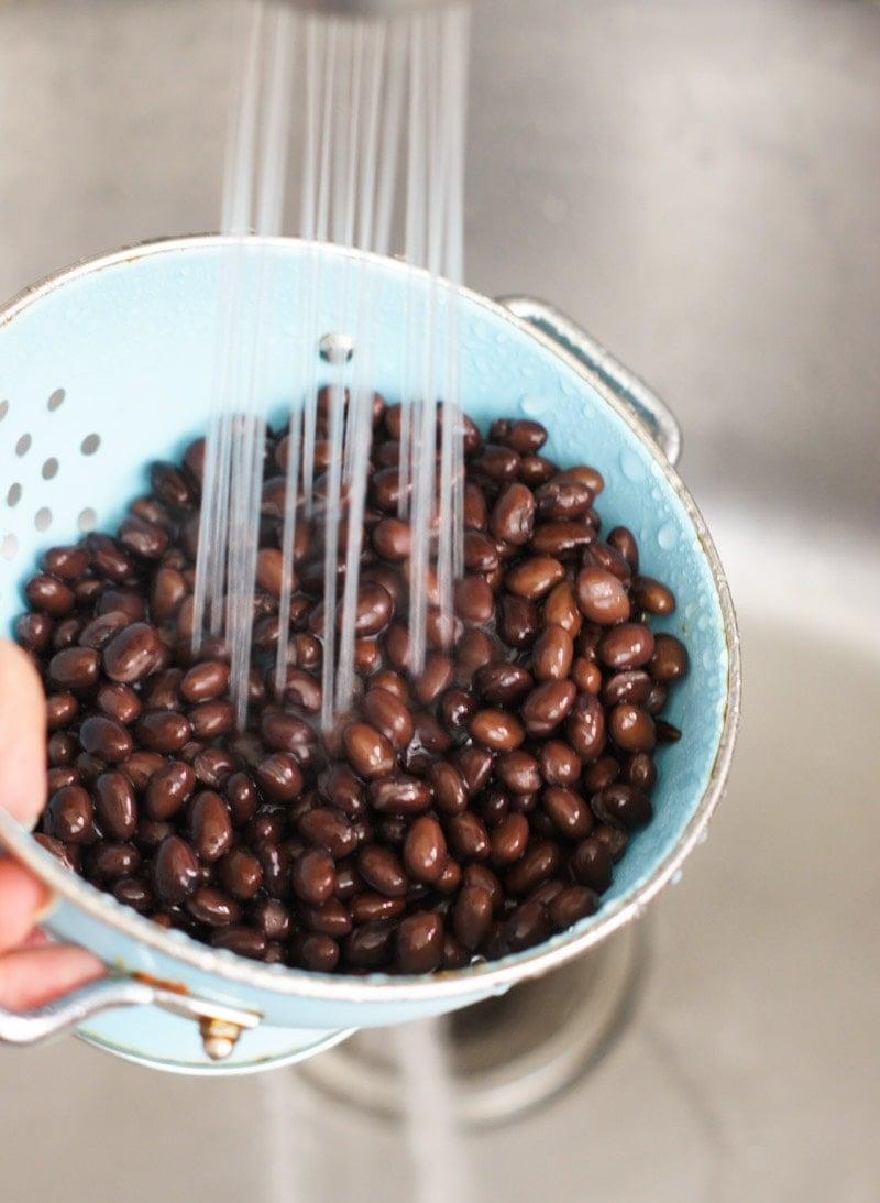 Rinsing beans in a colander under running water.