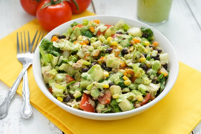 The salad in a bowl with the cilantro avocado dressing.