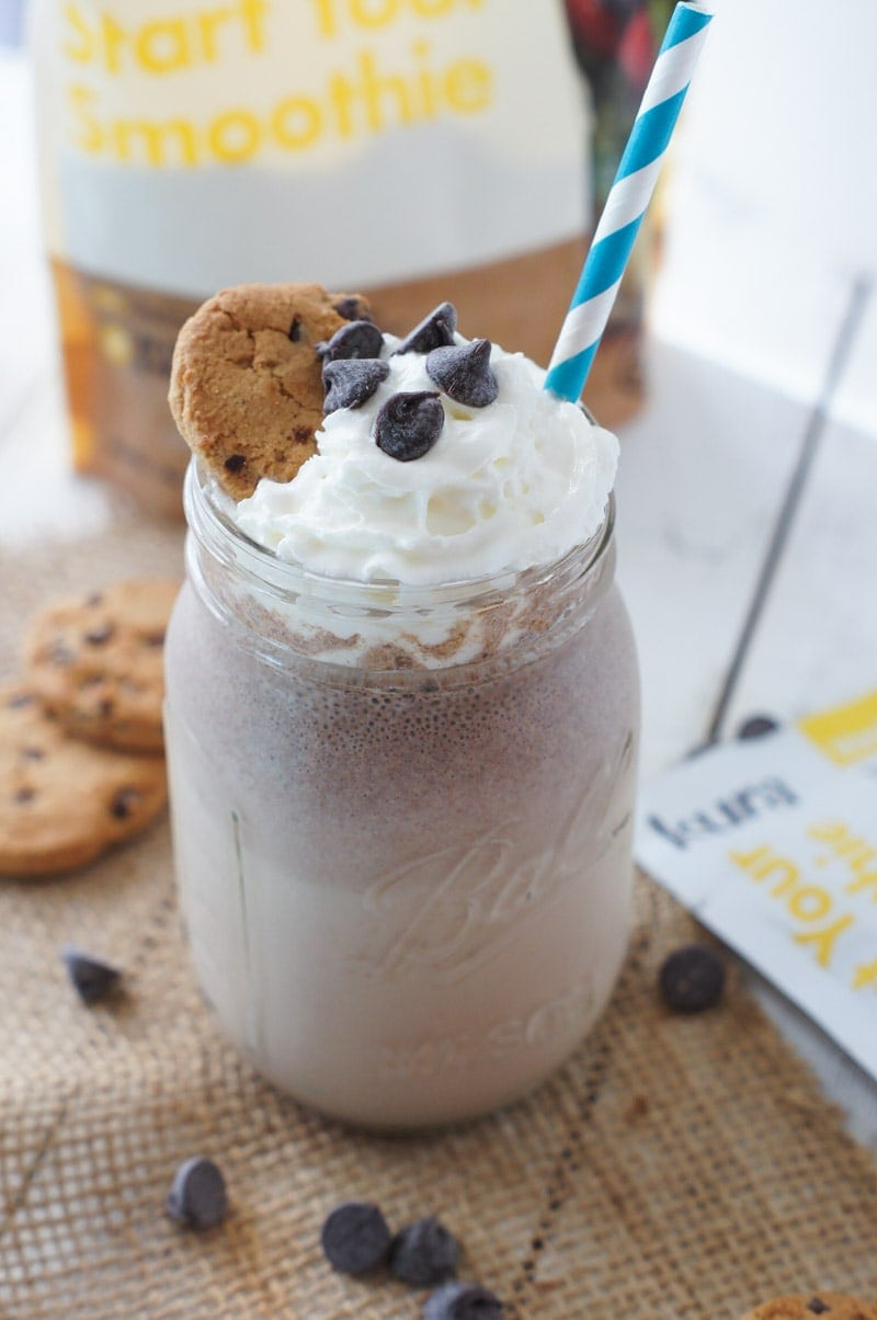 A smoothie topped with whipped cream, chocolate chips and a cookie.
