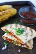 Two halves of a grilled BBQ chicken quesadilla topped with sliced green onions.