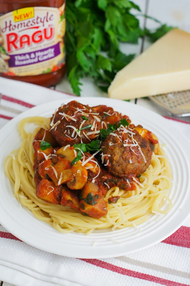 Mushroom and zucchini bolognese with meatballs served on spaghetti.