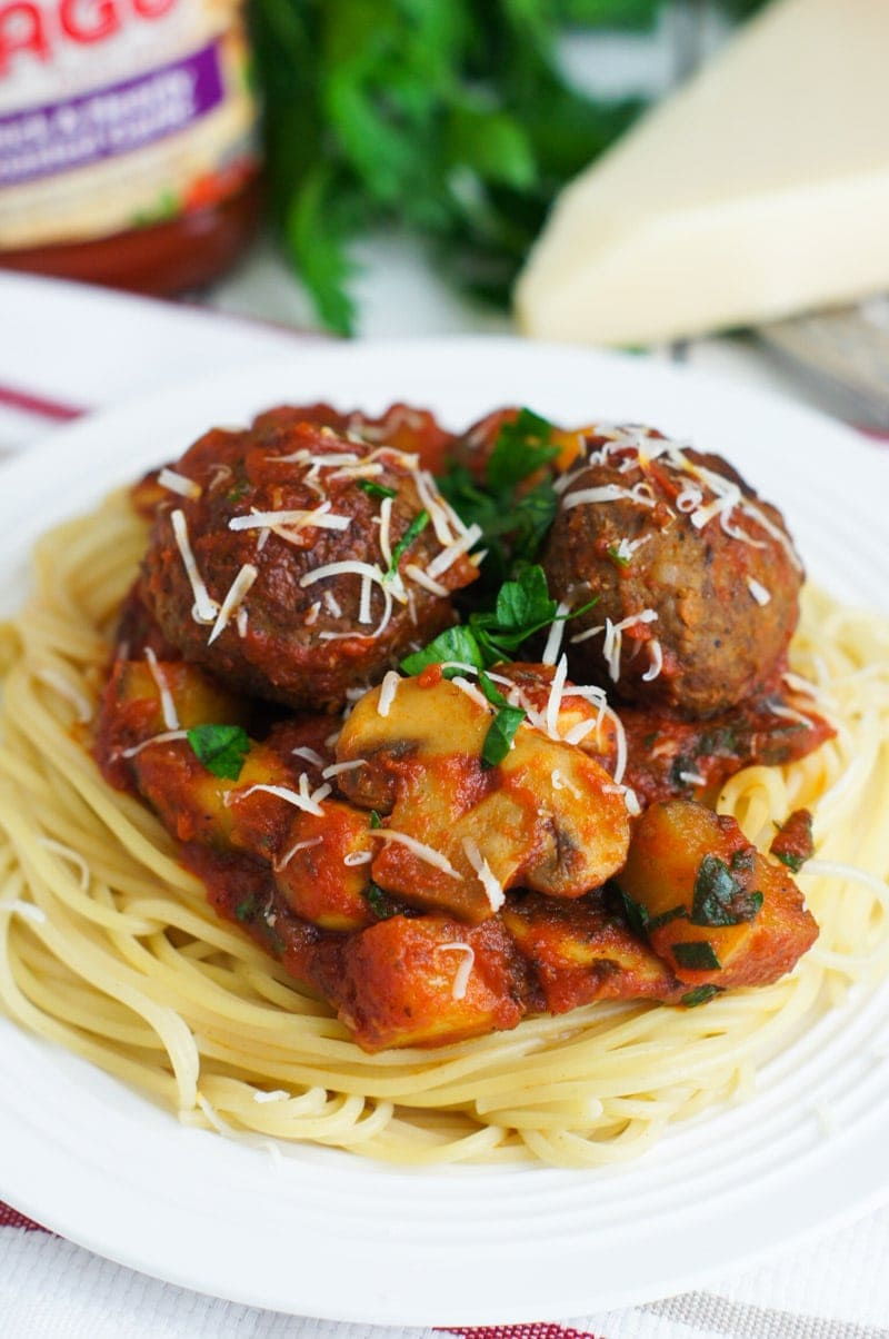 Spaghetti on a plate topped with bolognese and meatballs.
