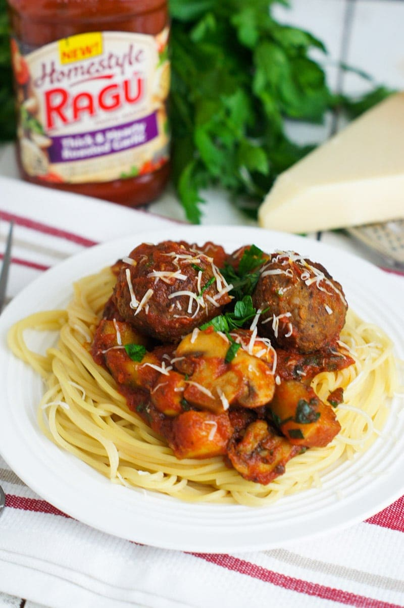 Meatballs and bolognese served on a plate on top of spaghetti.