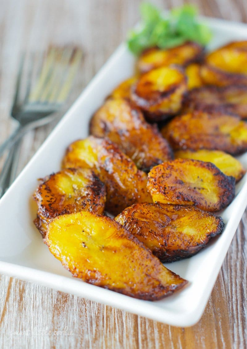 Golden Fried Sweet Plantain Slices (Platanos Maduros Fritos) served in a white pate.