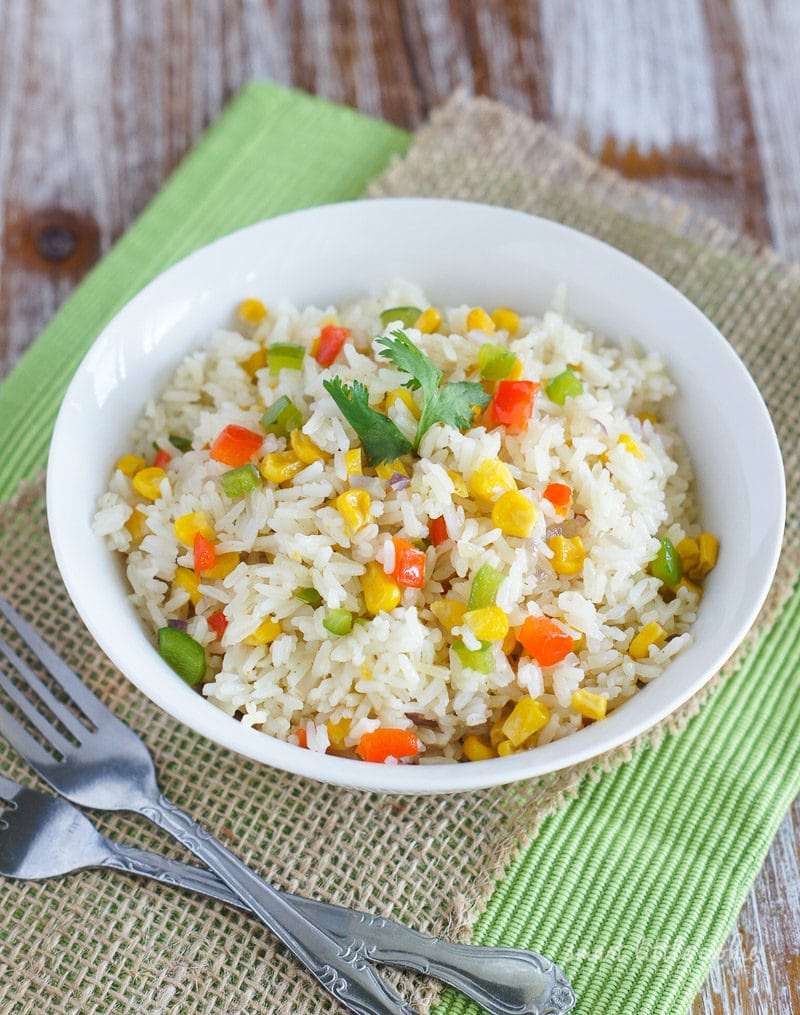 Rice and vegetables served in a white bowl next to two forks.