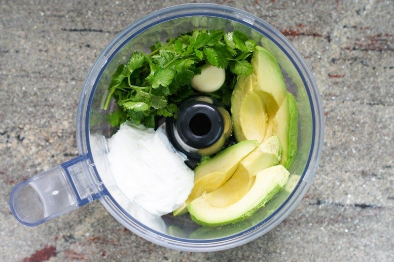 Aguacate, cilantro y ajo en un procesador de comidas.