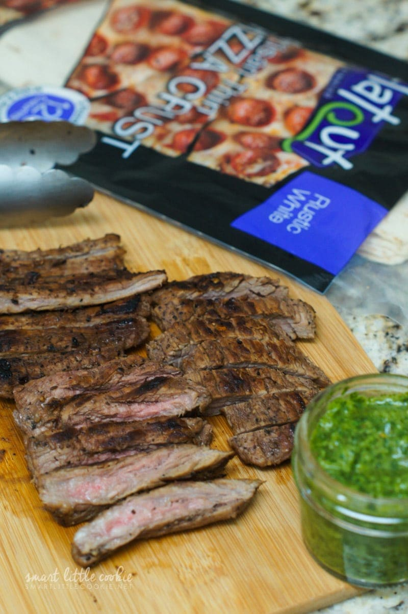 Slices of steak on a wooden chopping board.