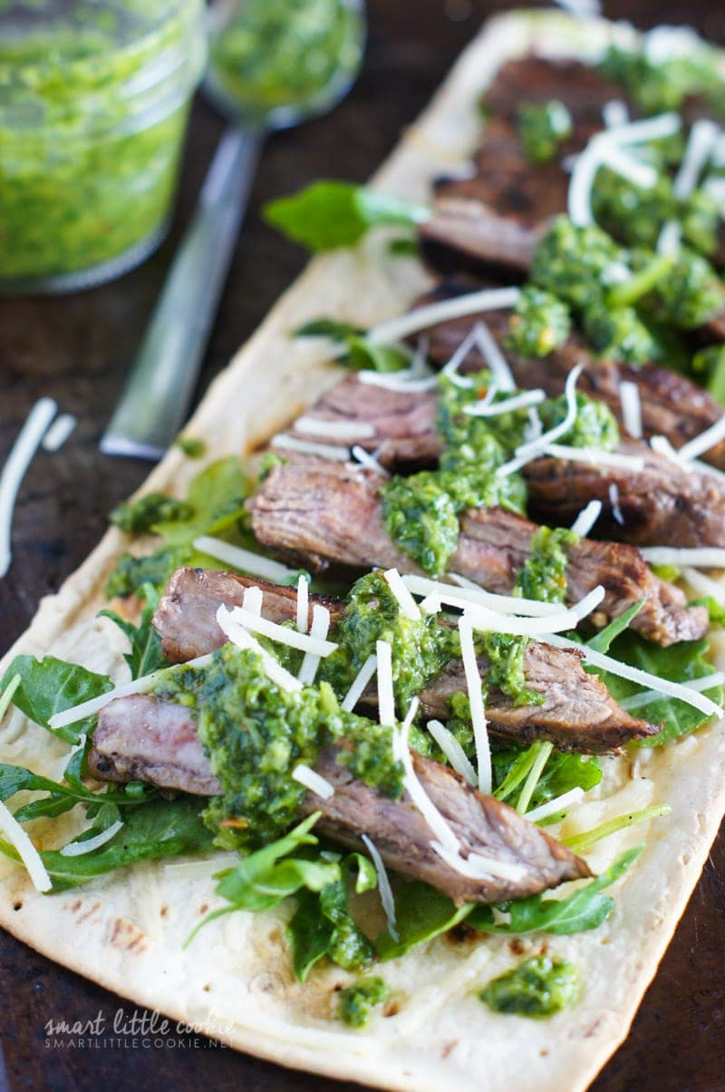Close up of strips of steak topped with chimichurri and parmesan.