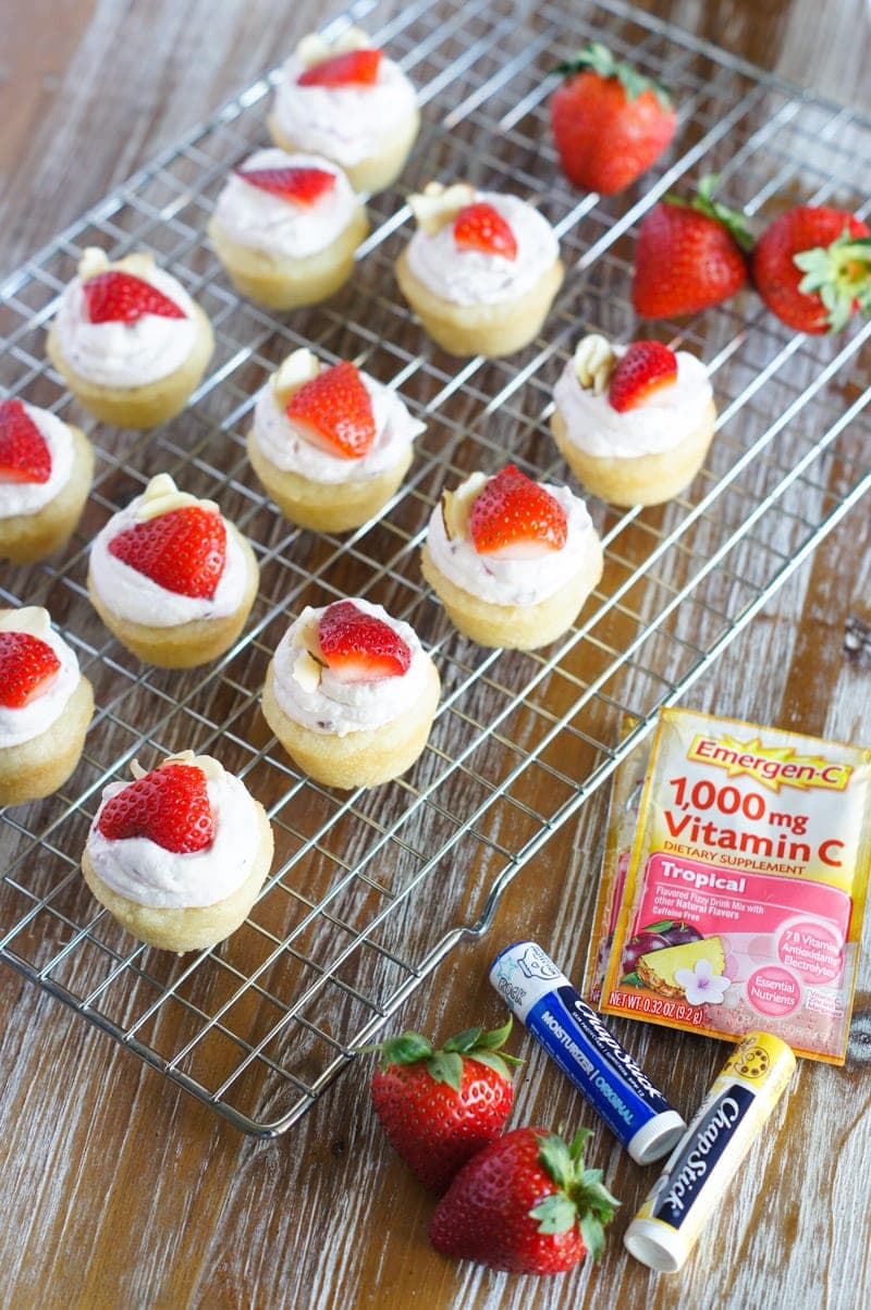 Twelve strawberry cheesecake bites on a cooling rack.