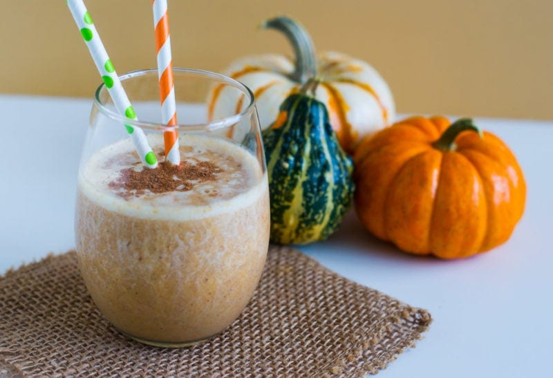 A smoothie next to three small pumpkins.