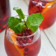 Pomegranate sangria in a glass garnished with a mint sprig.