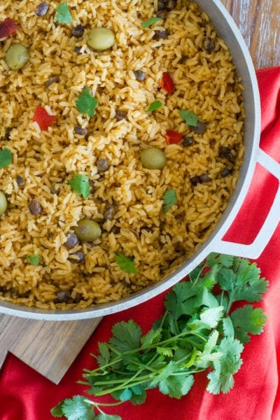 Pigeon peas and rice in a large pot served on a wooden table.