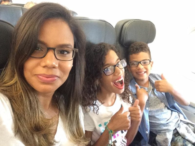 A woman and two children on a plane.