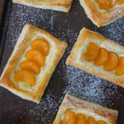 Mandarin and cheese pastelitos on a baking sheet dusted with powdered sugar.