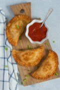 Three chicken parmesan empanadas on a wooden board with a red sauce.
