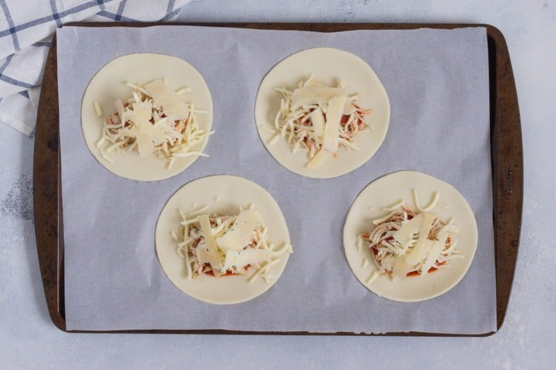 Four discs of empanada dough topped with the filling before being folded.