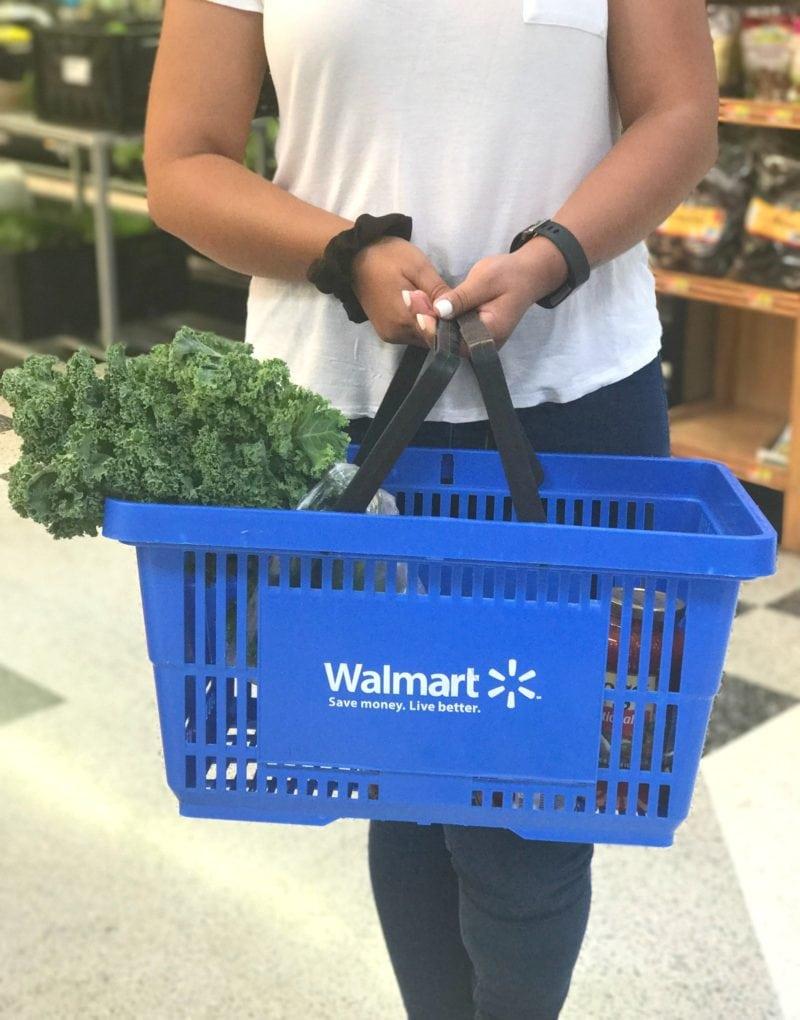 A woman holding a Walmart shopping basket.
